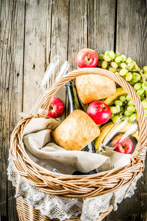 Picnic basket with food and drinks (fresh fruits, bread and wine bottle, glasses), copy space 스톡 콘텐츠