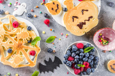 Halloween kids food treat. Funny pancakes - ghosts, jack o Lantern pumpkins, spider webs. Breakfast snack for childs Halloween party, with berries & candy,  gray stone table top view copy space 스톡 콘텐츠