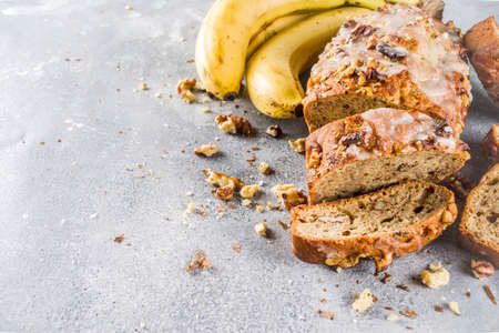 Homemade banana bread with walnuts, gray stone concrete background copy space, Vegan food.