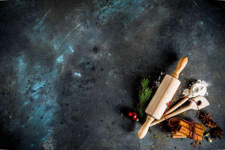Kerstbakkerijachtergrond, met bakgerei, meel, kruiden en decoraties, donkere betonnen tafel, kopieerruimte bovenaanzicht