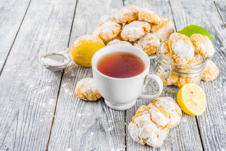 Lemon Crinkle Cookies, homemade sweet and sour baking with tea cup, white wooden background copy space