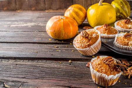 Homemade Autumn Pumpkin Spice Muffins with Pecan nuts. Fall and winter baking. Old rustic wooden background copy space.