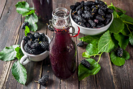 Mulberry Shrub, Juice or  liqueur in glass bottles, with fresh mulberries, rustic wooden background copy space