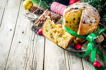 Traditional Christmas panettone with dried fruits and nuts, on old wooden background wth christmas decoration copy space top view
