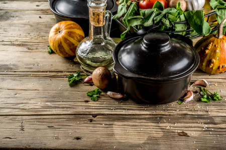 Autumn seasonal cooking concept. Various autumn vegetables (pumpkin,carrot,paprika,tomatoes,ginger) with pot for cooking soup. wooden background