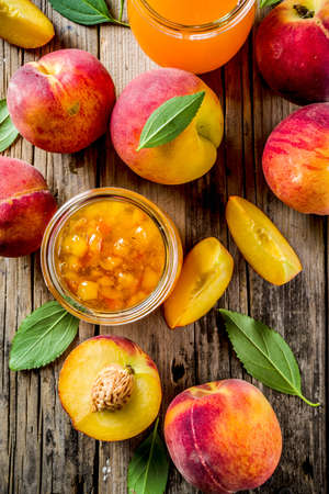 Homemade peach jam, with fresh organic peaches, rustic wooden background copy space