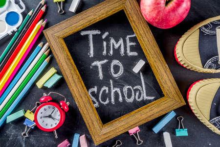 School education supplies on black chalkboard backdrop. Back to school concept.