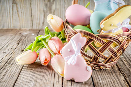 Easter holiday greetings basket with pastel colored eggs, Easter baking cupcake cookies, spring flowers.