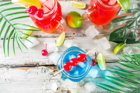 Summer tropical cold drinks. Blue Hawaiian, Tequila sunrise, Sea breeze cocktails over light blue wooden beach background, copy space 스톡 콘텐츠