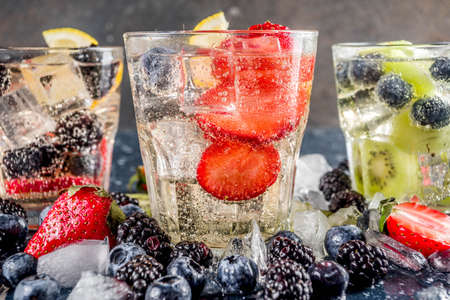 Summer fruits and berry cold cocktail, Lemonade, infused water with blueberries, strawberries, blackberries, kiwi. lemon. Dark blue concrete background copy space 스톡 콘텐츠