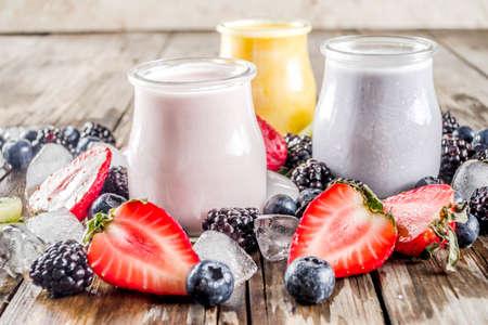 Summer fruits and berries smoothie drink. Vitamin diet snack beverage, with blueberries, strawberries, blackberries, kiwi. Dark blue concrete background copy space 스톡 콘텐츠