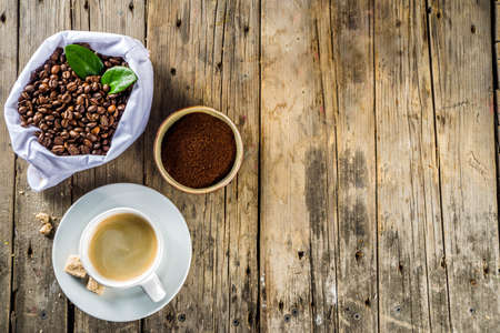Cup of espresso with coffee beans. ground coffee and leaves on rustic background  Stok Fotoğraf