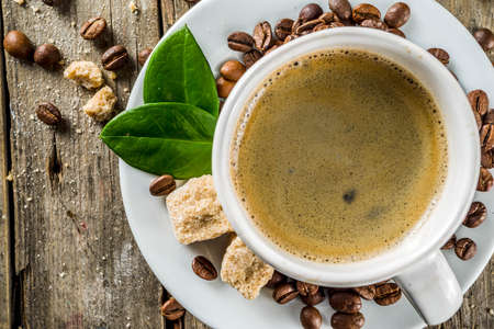 Cup of espresso with coffee beans. ground coffee and leaves on rustic background  Stock fotó