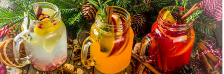 Autumn winter sangria, mulled wine or hot spiced cider cocktails. Red, white and orange hot winter drinks and beverages, in glass mason jar mugs with spices and citrus fruit. Om Christmas decorated rustic background copy space