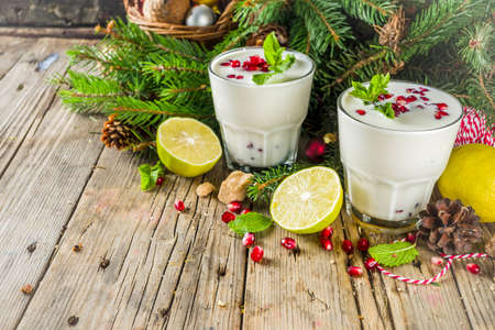White christmas mojito drink. with lemons, mint and pomegranate, rustic wooden background copy space