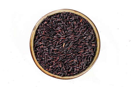Small bowl of organic black rice isolated on white background. Top view