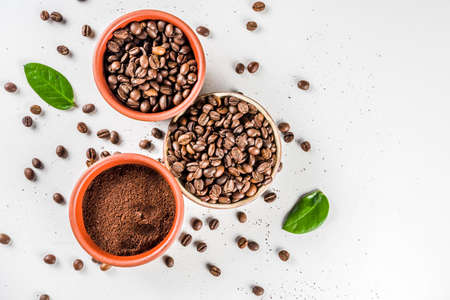 Small bowl of ground coffee and roasted coffee beans on white background, top view Imagens