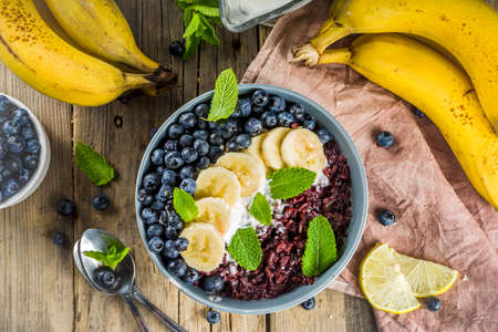 Black rice pudding breakfast bowl with fresh fruits and coconut milk, wooden background copy space