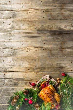 Poulet entier rôti traditionnel de Noël et de Thanksgiving avec des fruits et du romarin. Table de noël en bois rustique, avec des branches d'arbres de noël et un espace de copie de décorations