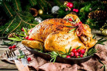 Traditionelles gebratenes ganzes Huhn zu Weihnachten und Thanksgiving mit Obst und Rosmarin. Rustikaler hölzerner Weihnachtstisch mit Weihnachtsbaumzweigen und Dekorationskopienraum Standard-Bild
