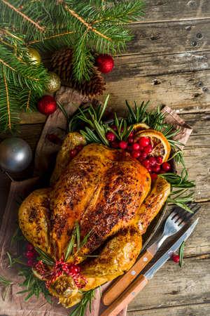 Traditionelles gebratenes ganzes Huhn zu Weihnachten und Thanksgiving mit Obst und Rosmarin. Rustikaler hölzerner Weihnachtstisch mit Weihnachtsbaumzweigen und Dekorationskopienraum