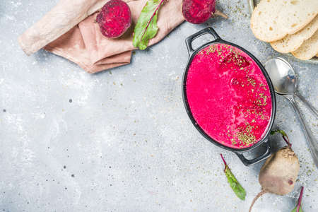 Autumn vegan vegetable food. Beet root cream soup on grey stone concrete background