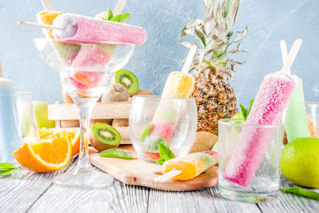 Colorful fruit ice cream popsicle. Juicy gelato lollypops on sticks, with different fresh tropic fruits, wooden background copy space Standard-Bild