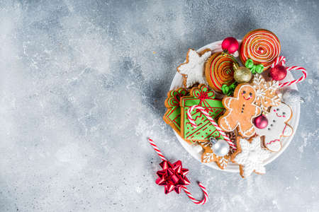 Homemade christmas sugar and gingerbread cookies decorated with colorful icing on grey stone background with Christmas tree branches and decorations