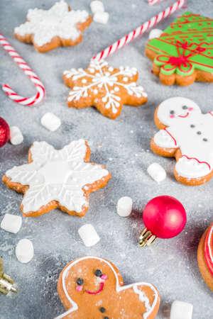 Biscuits faits maison de sucre et de pain d'épice de Noël décorés du glaçage coloré sur le fond gris en pierre avec des branches et des décorations d'arbre de Noël