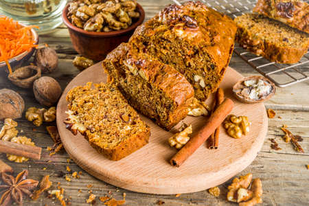 Homemade carrot cake with walnuts, rustic wooden background with ingredients, copy space Zdjęcie Seryjne