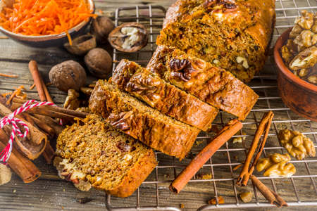 Homemade carrot cake with walnuts, rustic wooden background with ingredients, copy space Banco de Imagens - 133053563