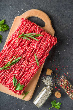 Raw minced beef meat with herbs and spices for cooking, black concrete or stone table