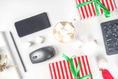 Office secret santa concept with Office table surface, keyboard, mouse, gift boxes and Christmas decoration white