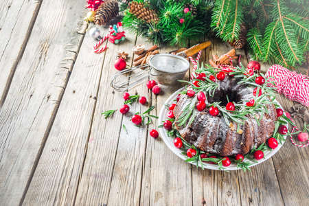 Homemade Christmas baking. Dark chocolate gingerbread christmas bundt cake with powdered sugar, fresh cranberries and rosemary, with xmas tree decoration Stock Photo
