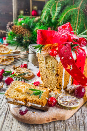Traditional Christmas and winter holidays baking. Fruit cake with icing, nuts, berry dry orange and rosemary. Sweet homebaked cake on old wooden background with Christmas decoration