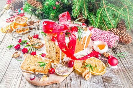 Traditionelles Weihnachts- und Winterferienbacken. Obstkuchen mit Zuckerguss, Nüssen, Beerentrockenorange und Rosmarin. Süßer hausgemachter Kuchen auf altem Holzhintergrund mit Weihnachtsdekoration Standard-Bild