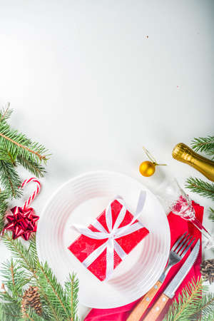 Christmas festive table setting with with a plate, fork, Christmas decorations, gift boxes, fir tree branches, glass and champagne bottle. Holiday table background copy space Stock Photo