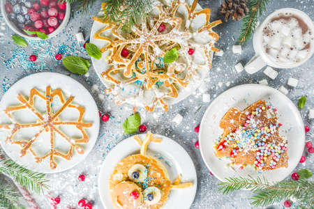 Various funny kid Christmas breakfast pancakes set - in form of snowflakes, Christmas tree, snowman, santa deer, mouse, With xmas decoration copy space Stock Photo