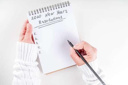 Woman hands ready to write list of her 2020 new year goals in notepad, top view flatlay copy space white background