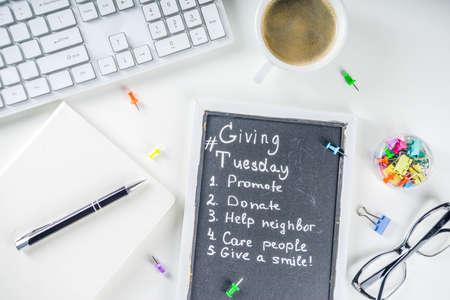 Chalk board with list of tasks, ideas, task for Giving Tuesday. Notes to various helping on Tuesday. International Charity Aid Day concept. White desktop flatlay copy space Stock Photo
