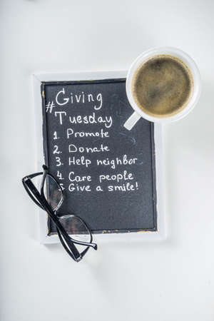 Chalk board with list of tasks, ideas, task for Giving Tuesday. Notes to various helping on Tuesday. International Charity Aid Day concept. White desktop flatlay copy space 写真素材