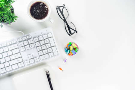 Office creative desk with supplies and coffee cup. White office table with keyboard, blank notebook, glasses, supplies and coffee cup. Flatlay layout copy space top view