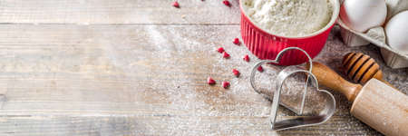 Valentine day baking background. Ingredients for cooking Valentine's heart cookies. Flour, eggs, sugar, spices on wooden background with red flower roses. Top view copy space.