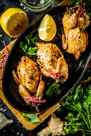 Delicious fried roasted quails with herbs, spices and greens. Grilled quails carcasses in a baking dish. Holiday Christmas and Thanksgiving meal concept. Stock Photo
