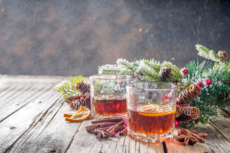 Christmas winter alcohol drink. Orange, spice and bourbon whiskey alcoholic cocktail in two glasses, wooden background with christmas tree branches and decor, copy space