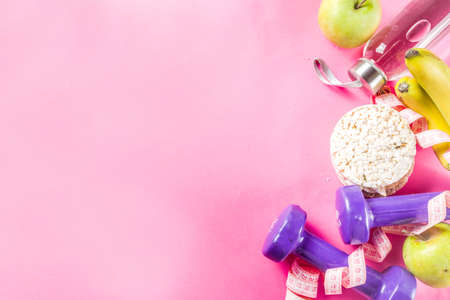 Fitness and healthy food concept. Dumbbells, fruits, water bottle, towel. Top view with copy space