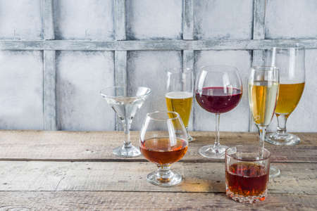 Selection of different alcoholic drinks - beer, red white wine, martini, champagne, cognac, whiskey in various glasses