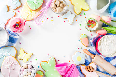 Sweet Easter baking cooking background with traditional Easter bunny and egg cookies, sugar sprinkles, ingredients, utensils. White table background copy space layout