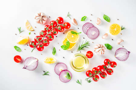 Cooking background with spices, vegetables and herbs fresh basil, rosemary, tomato, garlic, onions, lemon on a white kitchen table. Layout top view copy space. Healthy ingredients for cooking