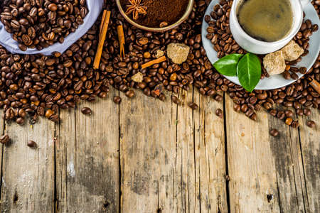 Cup of espresso with coffee beans. ground coffee and leaves on rustic background  Imagens